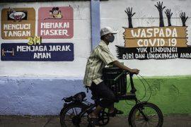 Pada Rabu (16/9/2020) warga berjalan di depan sebuah mural berisi pesan peringatan penyebaran virus corona di Pettah, Jakarta. Mural ini dibuat untuk mengingatkan masyarakat agar menggunakan protokol kebersihan saat beraktivitas, mengingat kasus COVID-19 yang banyak terjadi di seluruh negeri. Foto / Aprilio Akbar / aww.