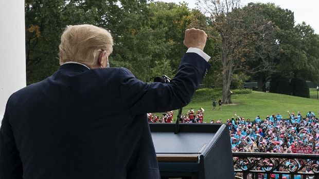Dengan dua perban di tangan, Presiden Donald Trump menunjuk dari balkon Ruang Biru Gedung Putih saat dia berbicara kepada kerumunan pendukung di Washington, DC, pada hari Sabtu, Oktober 2020.  (Foto AP / Alex Brandon)