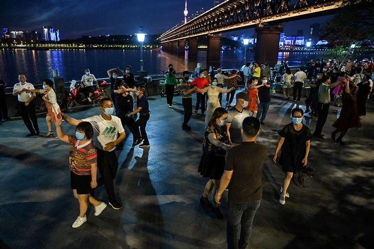 Pasangan bertopeng itu menari pada Selasa (12/5/2020) di sebuah taman di sebelah Sungai Yangtze di Wuhan, Provinsi Hubei, China.  Penduduk Wuhan, yang telah bebas dari lockout yang diberlakukan oleh epidemi Pemerintah-19 sejak Januari lalu dan memasuki enam minggu, telah kembali beroperasi meskipun kondisi terbatas.
