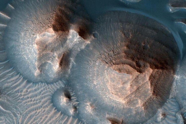 Beberapa kawah di Terra Arab dipenuhi dengan batuan Mars, yang sering muncul di punggung bukit yang membulat.  Di Mars Observatory Orbiter NASA, eksperimen itu direkam dengan kamera pencitraan resolusi tinggi.  Ilmuwan NASA mengkonfirmasi bahwa ada ribuan letusan gunung berapi purba di Mars.